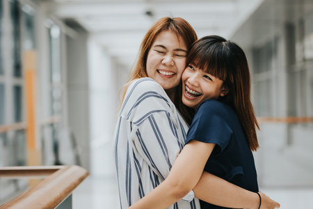 Two beautiful happy Asian girls friends laughing and hug. Friendship concept.