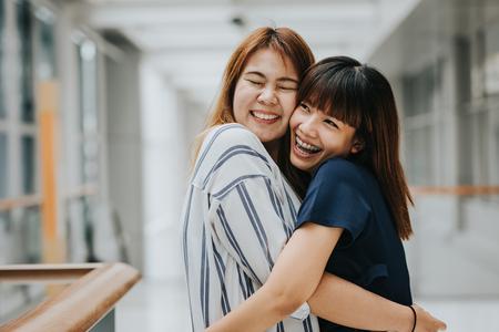 Dos hermosas niñas felices asiáticos amigos riendo y abrazo. Concepto de la amistad. Foto de archivo - 73005978