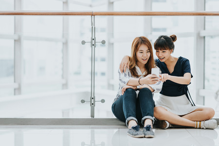 Young happy Asian girls best friends laugh and smile while having fun with smart phone mobile indoor. Archivio Fotografico