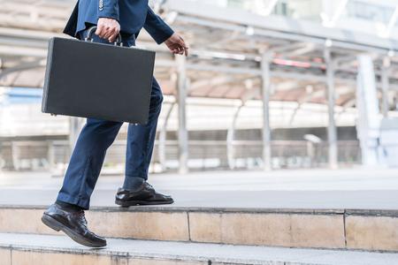 Close up disparo de hombre de negocios la celebración de maletín de cuero mientras caminaba hacia arriba en la escalera al aire libre en la ciudad. Foto de archivo - 74424965