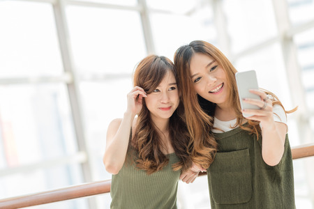 Young happy Asian girls best friends laugh and smile while taking selfie from smart phone mobile indoor. Archivio Fotografico