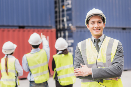 Confident businessman and team in logistic, export, import industry with shipping cargo container freight in background. Stock Photo