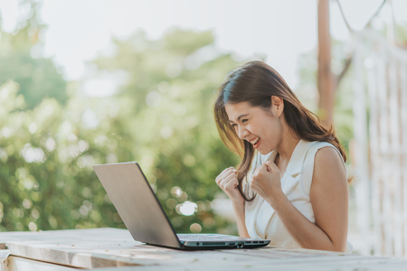 Feliz exitosa mujer asiática viendo portátil en el escritorio al aire libre Foto de archivo - 77733993