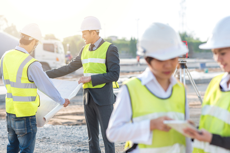 Engineer and builder review blueprint during team meeting at construction site in the morning with sunlight  Archivio Fotografico