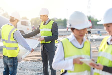 Ingenieur- und Erbauerreviewplan während der Teamsitzung an der Baustelle morgens mit Sonnenlicht Standard-Bild - 78170641