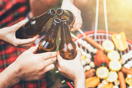 Friends clinking bottle of beer during camping outdoor with barbecue in background