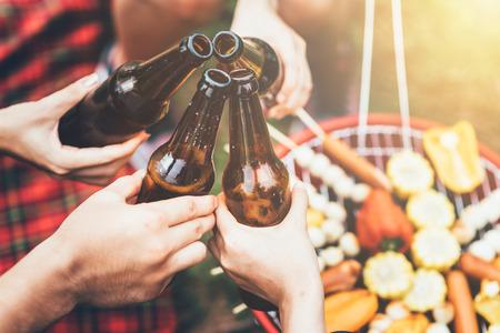 Vrienden klinken fles bier tijdens het kamperen buiten met barbecue in de achtergrond