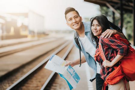 기차를 기다리는 기차역에서지도를 들고 행복 한 아시아 커플 여행자