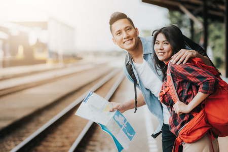 Happy Asian couple traveler holding a map at train station waiting for train