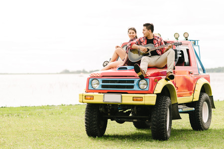 Happy Asian young couple in love playing guitar while sitting on a car during vacation Stockfoto