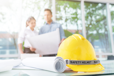 Close up shot of safety helmet and blueprint on workplace with engineer and architect discussing about new construction project in background Archivio Fotografico