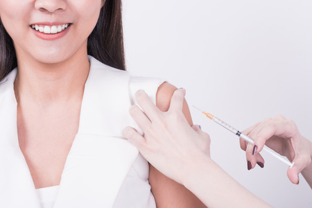 Close up hand using syringe to make vaccine injection to smile Asian female patient Stock Photo