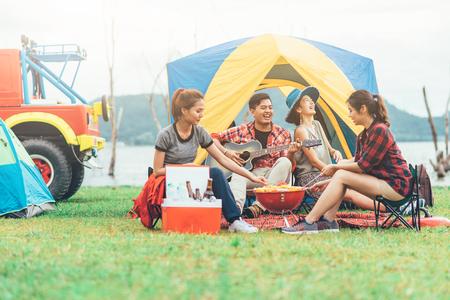 Grupo de amigos asiáticos que se divierten comiendo barbacoa al aire libre mientras acampan y tocan la guitarra. Foto de archivo