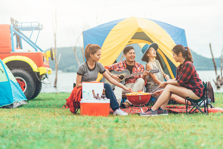 Group of Asian friends having fun eating barbecue outdoor while camping and play guitar.