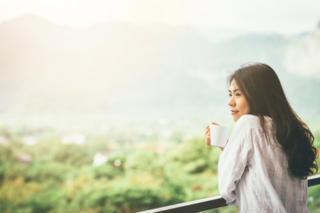 Asian woman drinking a cup of coffee and enjoy nature view in morining with sunlight