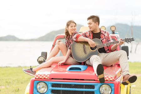 Asian couple having a good time playing guitar during vacation.