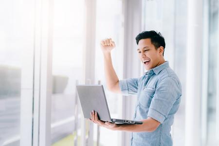 ハッピーは、ラップトップを保持していると彼の腕を上げる成功または達成を祝うために男性を興奮させた。