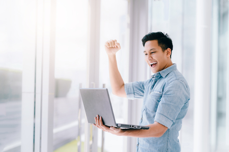 Happy excited Asian man holding laptop and raising his arm up to celebrate success or achievement.
