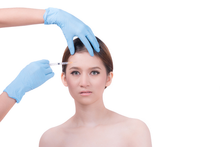 aging face: Beautiful Asian woman getting lifting botox injection in forehead from sergeant isolated on white background. Stock Photo