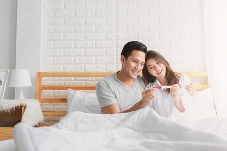 Feliz pareja asiática sonriendo después de averiguar la prueba de embarazo positiva en el dormitorio en casa