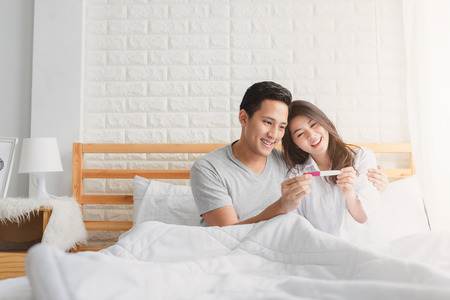 Happy Asian couple smiling after find out positive pregnancy test in bedroom at home