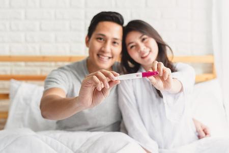 Foto de la feliz pareja asiática que muestra una prueba de embarazo positiva en el dormitorio. Concéntrese en el dispositivo de prueba de embarazo. Foto de archivo