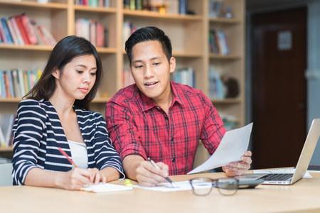 Two young Asian man and woman working together at the table. Start up business or study concept.