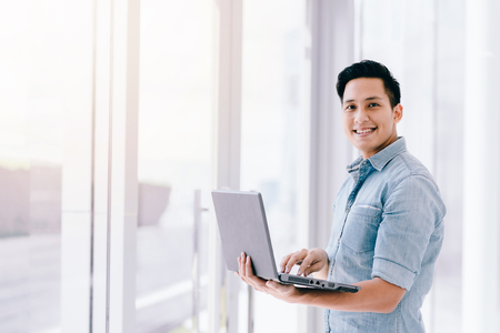 Happy smile Asian man using laptop with positive feeling in office. business success concept.