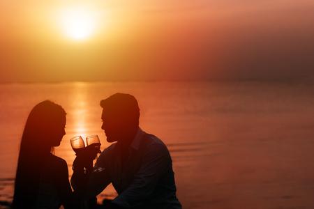 Silhouet van paar in liefde het drinken van wijn tijdens romantisch diner bij zonsondergang op het strand