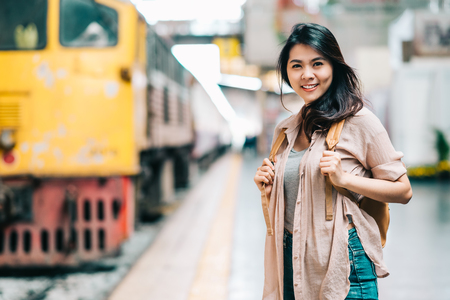 Happy beautiful traveler Asian woman with backpack at train station ready to start her journey.