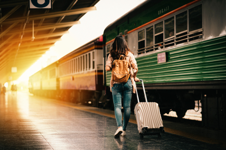 Woman traveler tourist walking with luggage at train station. Active and travel lifestyle concept Stockfoto