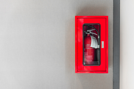 fire extinguishers cabinet on grey wall background in office building 스톡 콘텐츠
