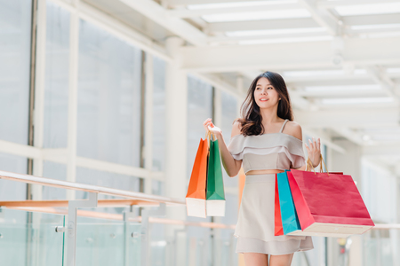 Portrait of happy young Asian woman with shopping bags walking in the mall 스톡 콘텐츠