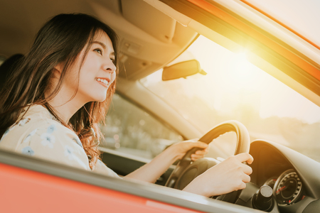 Confident and smile beautiful Asian woman driving a car in morning sunlight