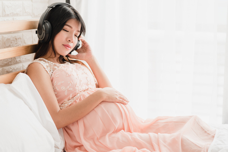 Happy Asian pregnant woman sitting on the bed listen to music in headphones Banque d'images