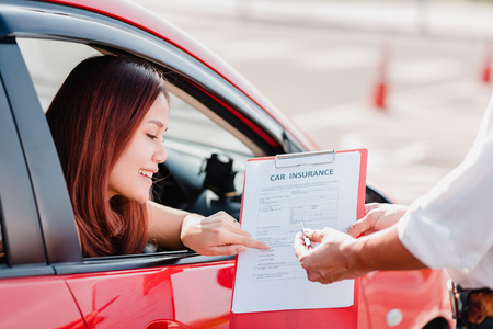 Insurance agent hand over car insurance document to asian woman client in car Stock Photo