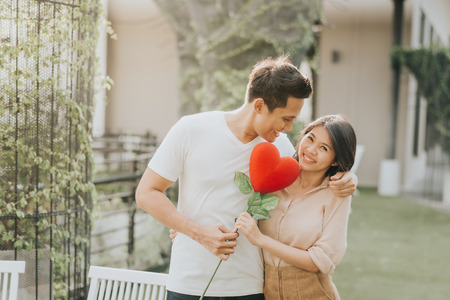 Romantic happy Asian couple in love having fun with heart flower while hugging. Vanlentine day concept. Archivio Fotografico