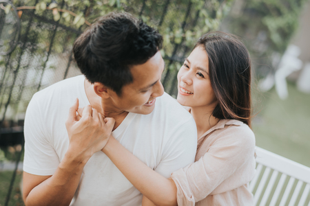 Happy Asian couple in love smiling and having fun while hugging outdoor.