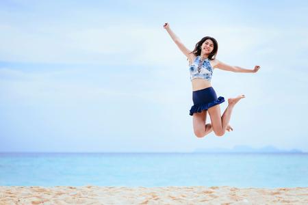 Gelukkige en vrolijke jonge Aziatische vrouw die op het strand in ochtend springt