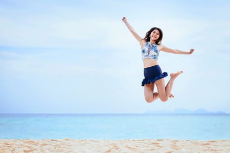 Happy and cheerful young Asian woman jumping on the beach in morning Stock Photo