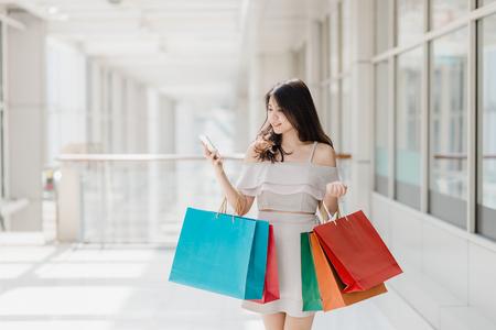 Mooie jonge gelukkig Aziatische vrouw met kleurrijke boodschappentas met behulp van smartphone tijdens het winkelen in winkelcentrum