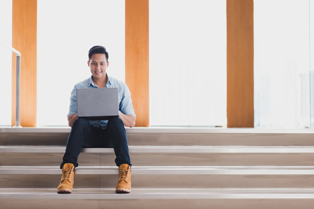 Happy young Asian man using laptop while sitting on the stair in office building.