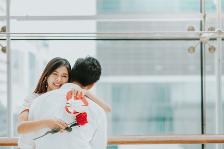 Happy  beautiful young Asian woman embracing her boyfriend after receive valentine gift and rose