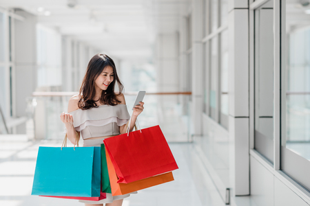 Beautiful young happy Asian woman with colorful shopping bag using smartphone while shopping in mall