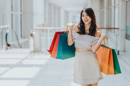 Happy Asian beautiful woman enjoying and smiling with colorful shopping bag in her both hand in mall.
