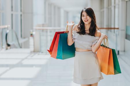 Glückliche asiatische Schönheit, die mit bunter Einkaufstasche in ihrer beiden Hand im Mall genießt und lächelt. Standard-Bild