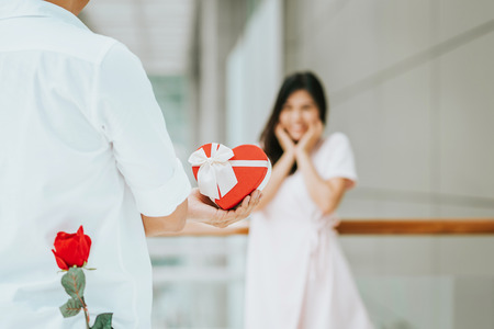 Rear view of a young man give present gift box with rose behind his back to his lovely girlfriend who look surprise Foto de archivo