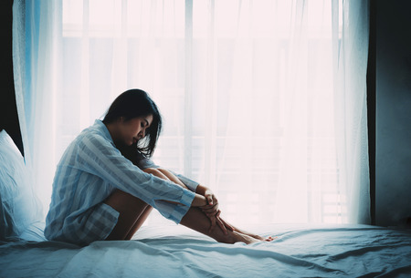 Unhappy beautiful Asian woman sitting on a bed looking sad and lonely 스톡 콘텐츠
