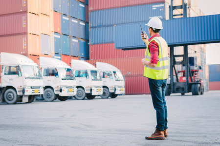 Asian foreman control loading Containers box for Logistic Import Export in dock Stockfoto