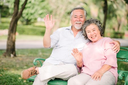 Happy Asian senior couple waving hand and smiling outdoor in the park